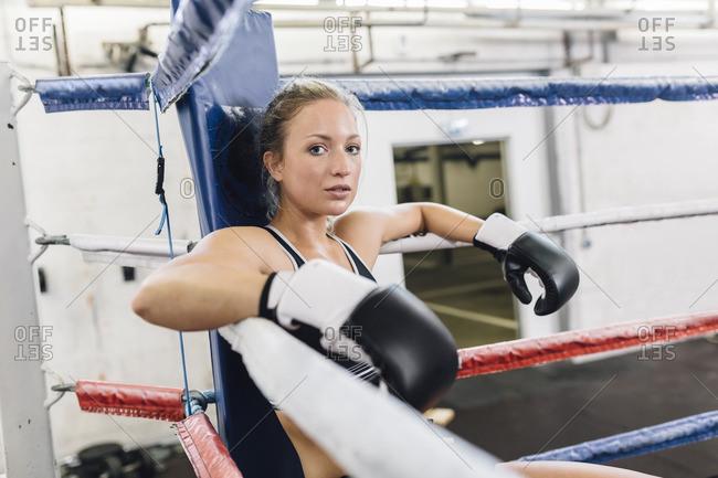 Portrait of female boxer resting in ring corner
