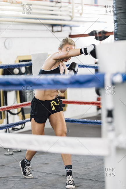 Female boxer punching in boxing ring