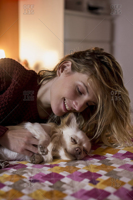 Woman lying on bed playing with her dog