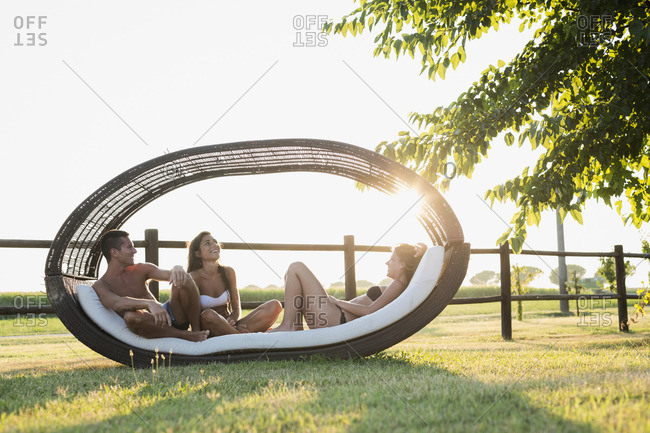 Three friends in swimwear relaxing in garden lounger