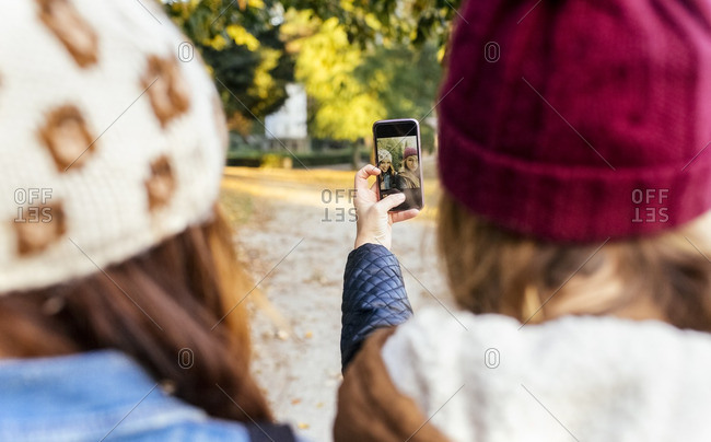 Two young women taking a selfie in a park in autumn