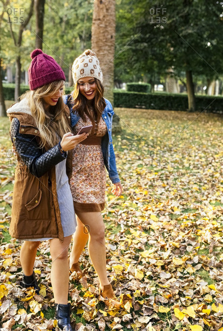 Two young women with smartphone walking in a park in autumn