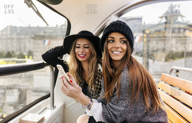 France- Paris- two smiling women with cell phone on a tour bus