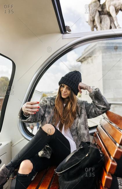 France- Paris- smiling woman taking a selfie on a tour bus
