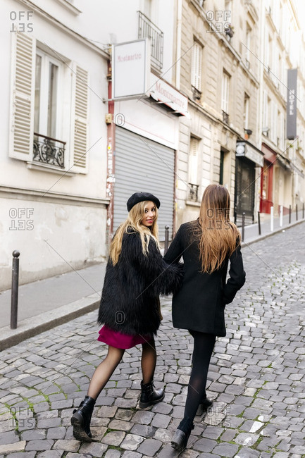 France- Paris- two young women walking on the streets of Montmartre