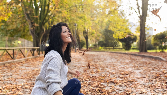 Happy young woman playing with leaves in a park in autumn