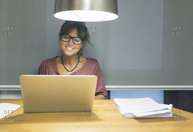 Smiling woman using laptop at desk