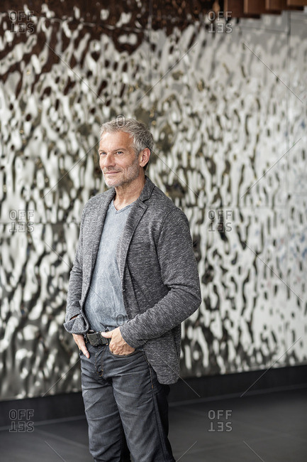 Confident businessman in front of rippled wall