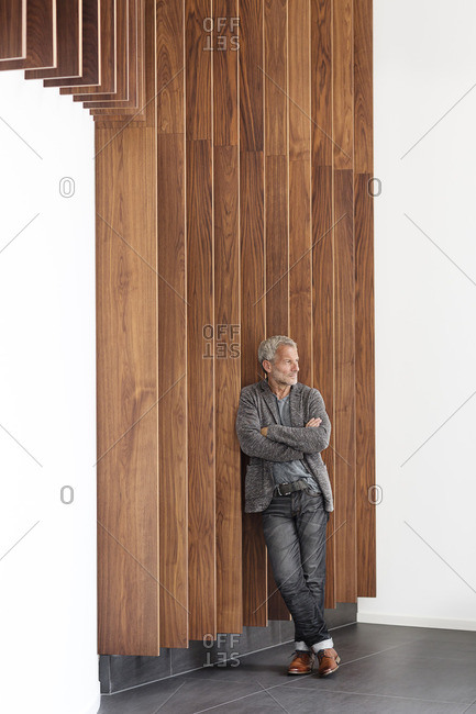 Confident businessman leaning against a wooden wall