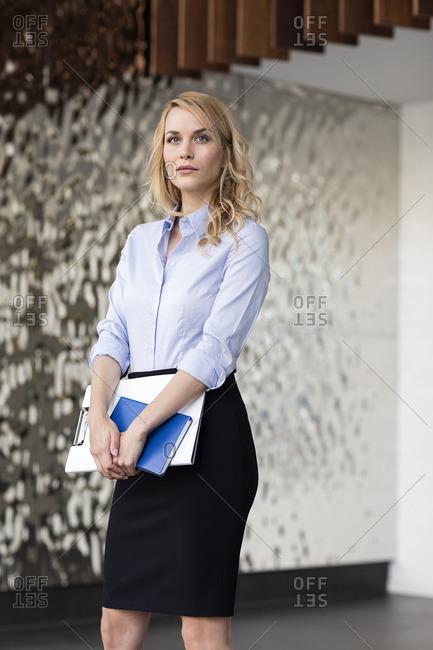 Confident businesswoman holding folder