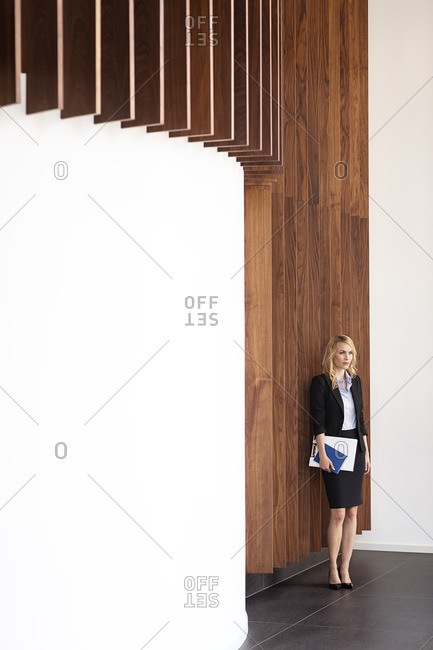 Businesswoman at wooden wall holding folders