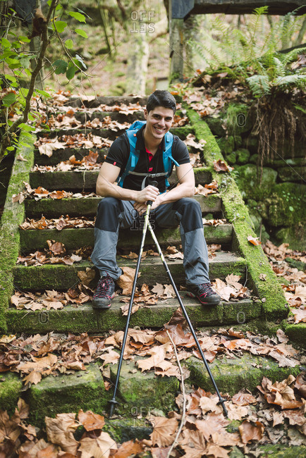 Smiling hiker sitting on stairs having a break