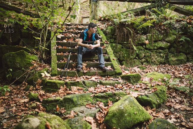 Hiker sitting on stairs having a break