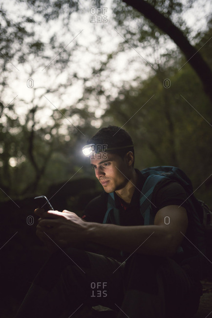 Hiker with a headlamp in the forest looking on smartphone
