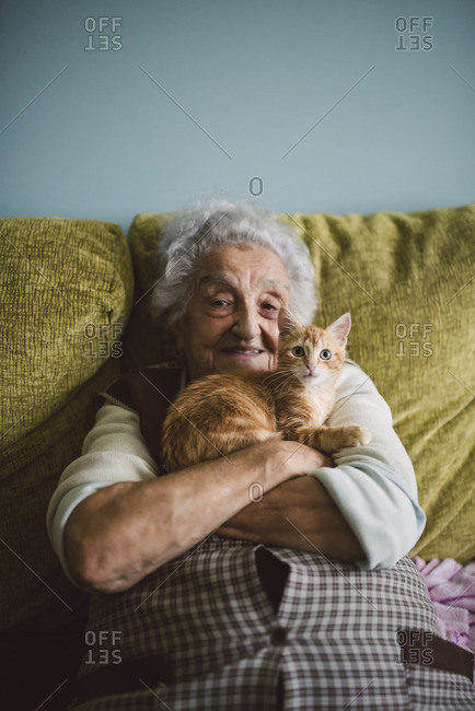 Portrait of happy senior woman cuddling with her cat on the couch