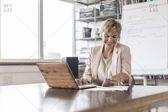 Smiling businesswoman with cell phone and laptop in modern conference room