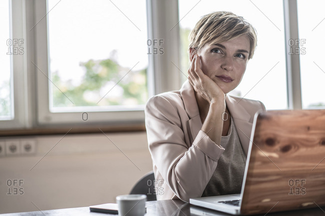 Businesswoman with laptop in conference room thinking