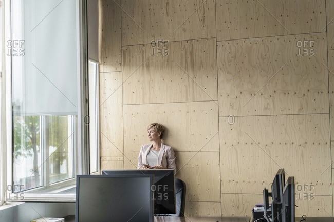 Smiling businesswoman with cell phone in office
