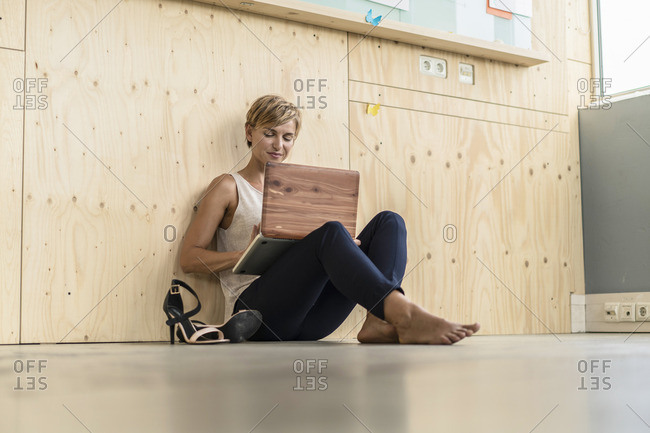 Businesswoman using laptop on the floor