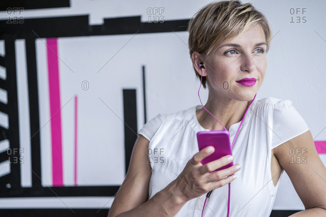 Woman in modern office listening to music on smartphone
