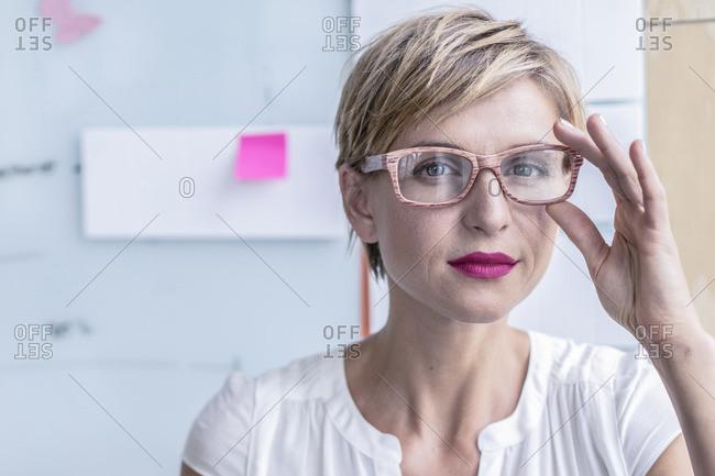 Portrait of businesswoman in front of whiteboard in modern office