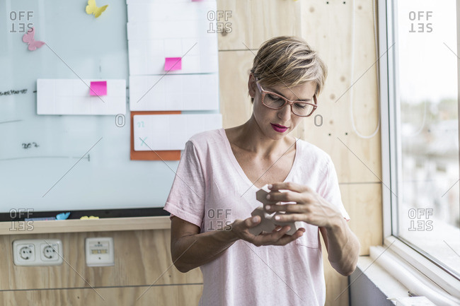 Woman working on wooden building blocks in modern office