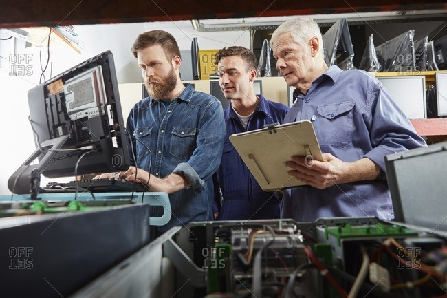 People in computer recycling plant checking desktop pc