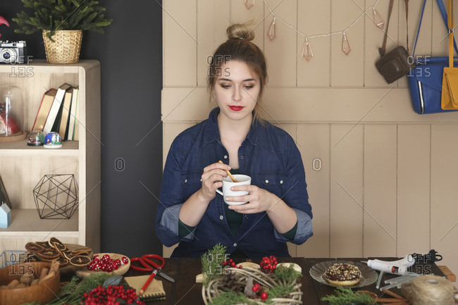 Woman drinking cup of coffee at her desk