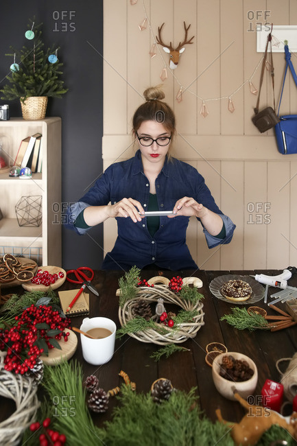 Woman taking picture of self-made Advent wreath with smartphone