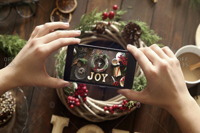 Woman's hands taking picture of self-made Advent wreath with smartphone