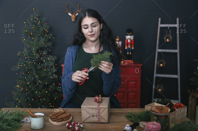 Young woman cutting twig for decorating Christmas present