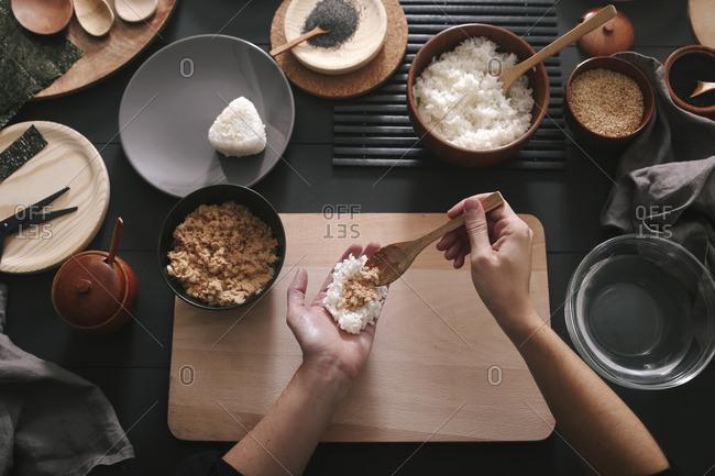 Woman's hands preparing Onigiris rice balls