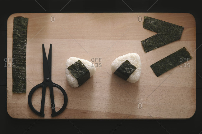 Onigiris- strips of nori and scissors on chopping board