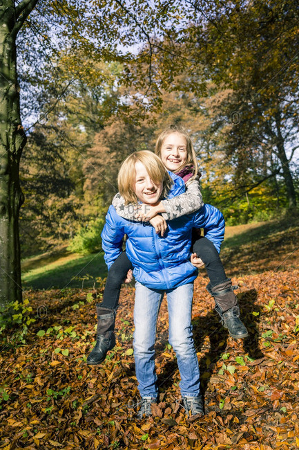 Portrait of boy giving his sister a piggy back ride in autumn