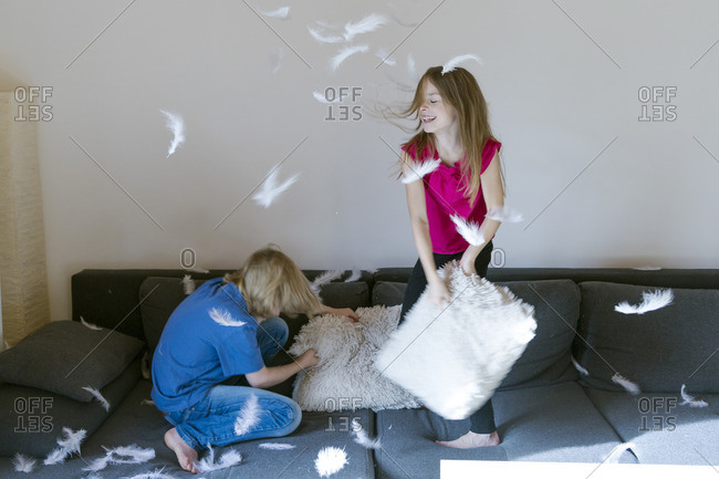 Pillow fight between brother and sister at home