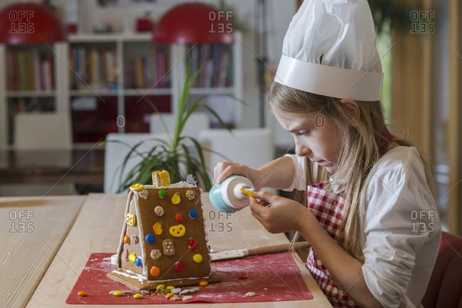 Girl garnishing gingerbread house