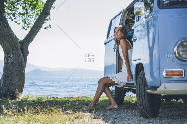 Italy- Lake Garda- smiling young woman in camping bus
