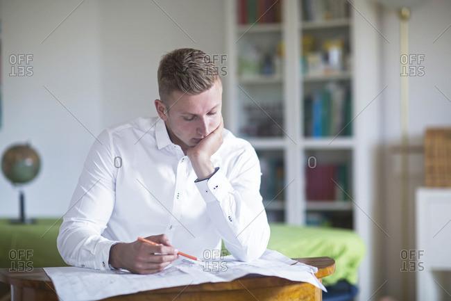 Young man looking at construction plan at desk