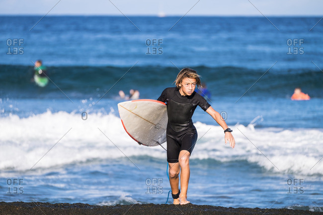 Spain- Tenerife- boy carrying surfboard at the sea