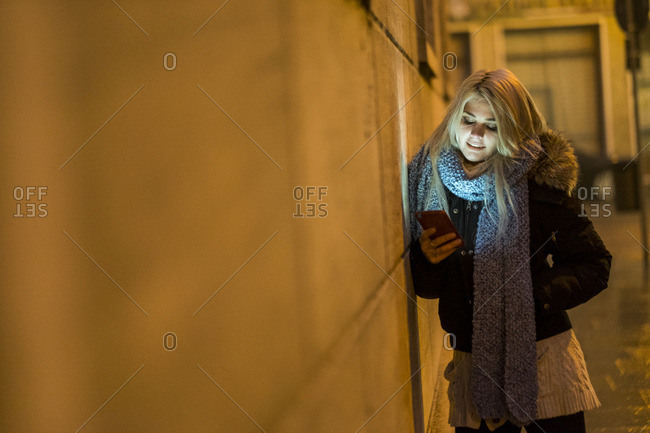 Young woman leaning against facade at night looking at her smartphone