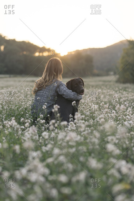 Young woman and her dog sitting in field of flowers at twilight