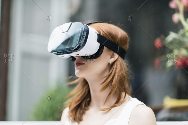 Redheaded woman wearing Virtual Reality Glasses