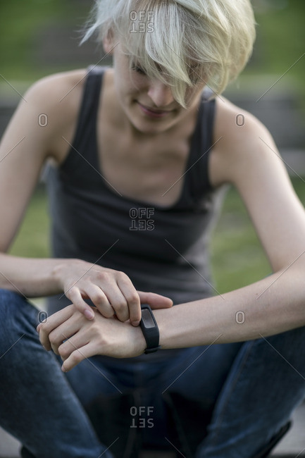 Smiling young woman checking her smartwatch