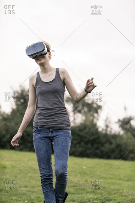Smiling young woman using Virtual Reality Glasses outdoors