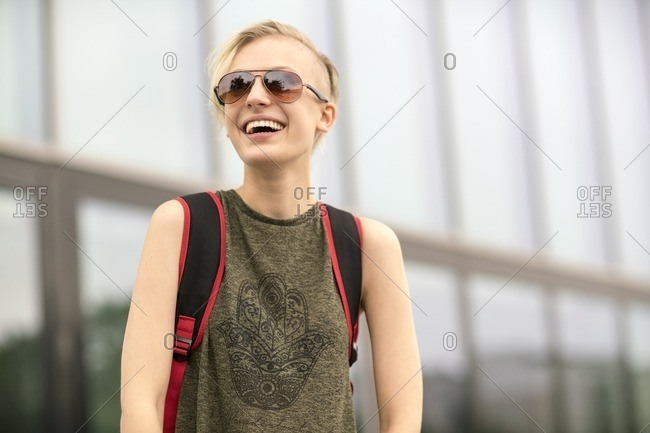 Portrait of laughing blonde woman wearing sunglasses