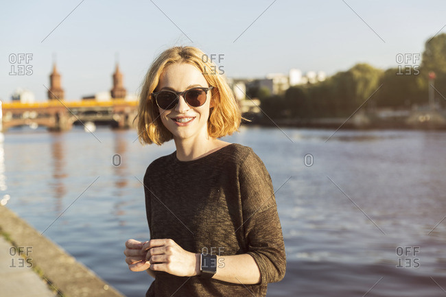 Germany- Berlin- portrait of smiling young woman wearing sunglasses and smartwatch