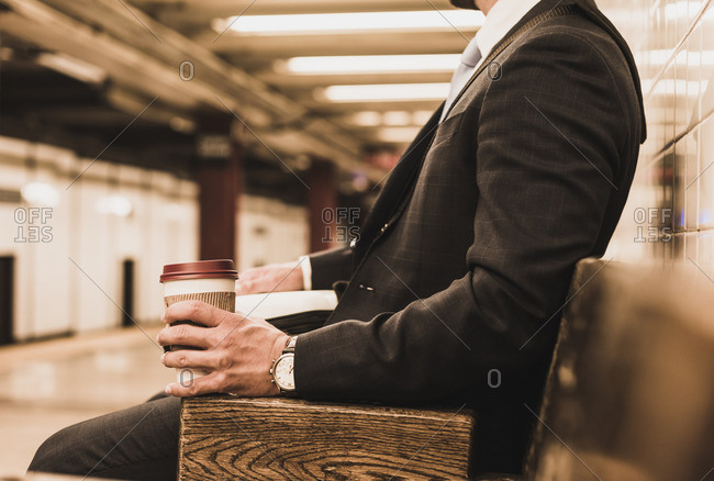 Young businessman waiting at metro station platform- holding disposable cup