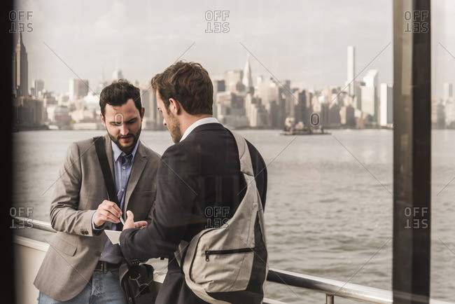 USA- New York City- two businessmen reviewing document on ferry on East River