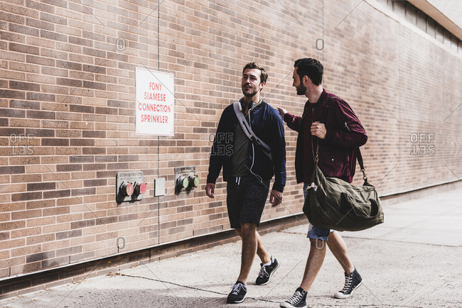two friends with bags walking on pavement stock photo offset