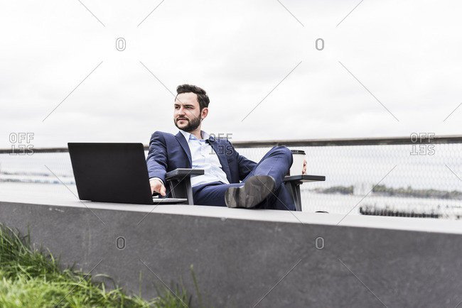 USA- New York- Manager in Manhattan sitting outdoor- using laptop